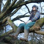 Young woman sat in the low hanging bough of a tree.